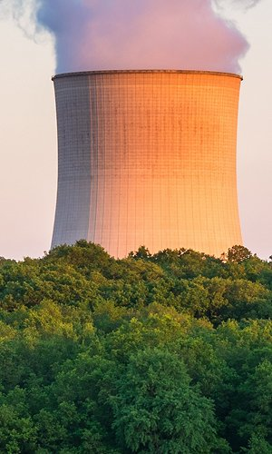 Steaming Cooling Towers at Nuclear Power Plant around Sunset