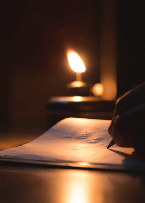 A student writing on notebook in a kerosene oil lamp